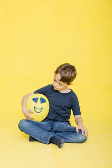 Full length of cute boy looking at yellow balloon with anthropomorphic face while sitting against colored background - JRFF04430