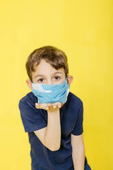 Portrait of boy wearing face mask while blowing a kiss against yellow background - JRFF04433
