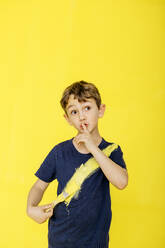 Cute boy using paintbrush on t-shirt while standing with finger on lips against yellow background - JRFF04439