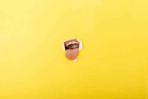 Close-up of boy sticking out tongue through torn yellow paper - JRFF04442