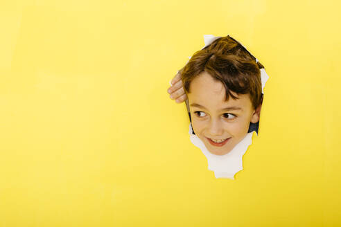 Smiling cute boy tearing yellow paper while looking away - JRFF04445