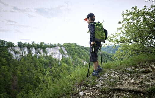 Boy standing with hiking poles at the edge of plateau while looking at landscape at Swabian Jura - DIKF00497