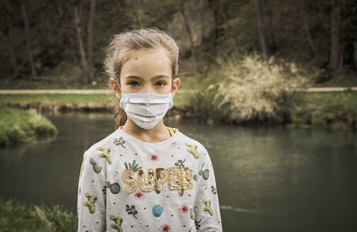Portrait of sad girl standing with self-sewn face mask at riverbank in forest - DIKF00500