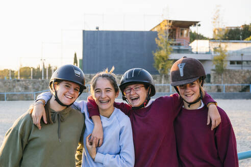Portrait of cheerful female jockeys standing together against training ground on sunny day - ABZF03118