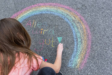 Girl painting rainbow on street with text 'Everything will fall into place' - SARF04557