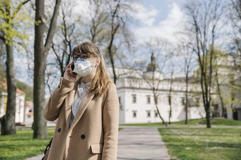 Woman wearing FFP2 mask and using smartphone in a park - AHSF02511