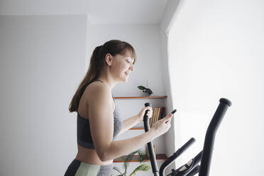 Woman using smartphone while performing workout on elliptical trainer at home - AHSF02523