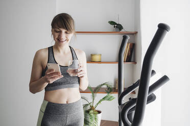 Woman drinking water and using smartphone after performing workout on elliptical trainer at home - AHSF02526