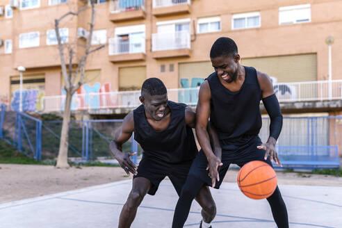 Basketball players playing basketball on court outdoors - EGAF00018