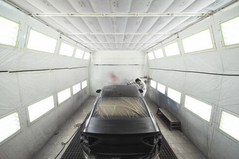 Body painter painting car in paint booth - SNF00013