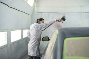 Body painter painting car in paint booth - SNF00016