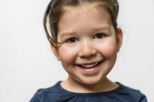 Portrait of happy girl against white background - MGIF00922