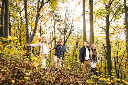 Boy and girl enjoying by parents in forest during autumn - WFF00395