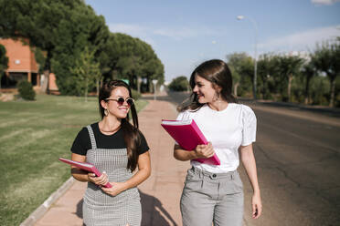 Happy female university students talking while walking on footpath at campus on sunny day - GRCF00187