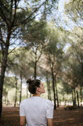 Rear view of young woman with hair bun looking away in forest - GRCF00190