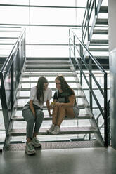Full length of young female students sharing smart phone while sitting on steps at university - GRCF00193