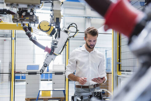 Young male expert using digital tablet while standing by robotic arm in industry - DIGF10414