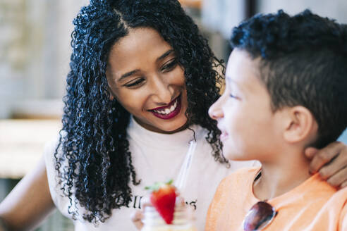 Smiling woman looking at boy drinking smoothie in restaurant - DGOF00945