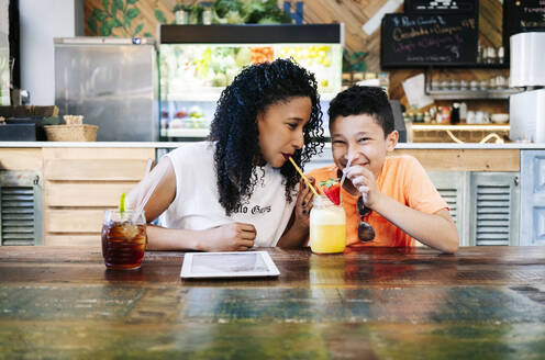 Cheerful boy and mother drinking smoothie at restaurant - DGOF00948