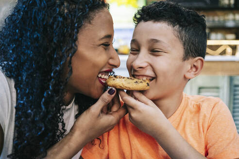 Close-up of cheerful mother and son sharing cookie while sitting at restaurant - DGOF00954