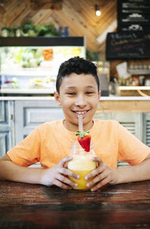 Portrait of smiling boy holding fresh smoothie while standing at table in restaurant - DGOF00957