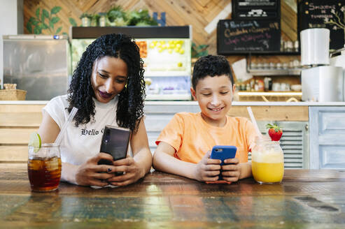 Smiling mother and son using smart phones while sitting at restaurant - DGOF00960