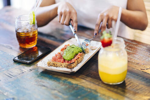 Midsection of woman eating meal while sitting with drinks at restaurant - DGOF00972