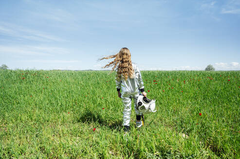 Rear view of girl in astronaut costume walking with helmet on grass - JCMF00702
