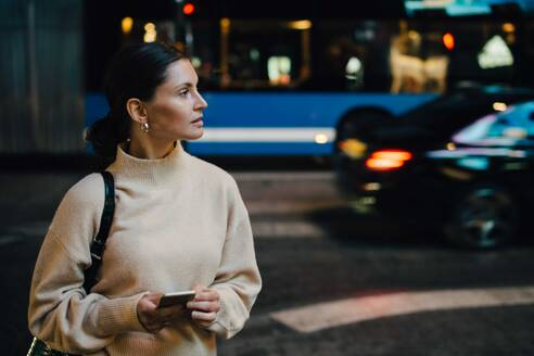 Woman with cellphone looking away while standing in city at night - MASF17940