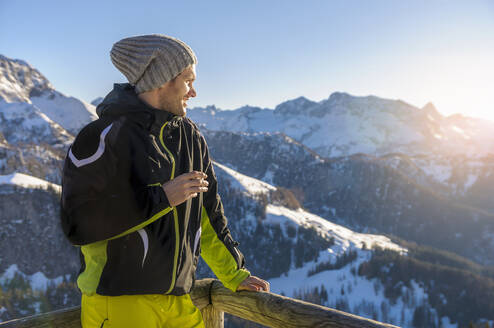 Man standing by railing while looking at snowcapped mountains against sky - DIGF10464