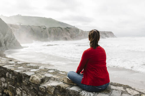 Full length rear view of relaxed tourist sitting on retaining wall while looking at cliffs against sky, Itzurun, Zumaia, Spanish Basque Country, Spain - XLGF00140