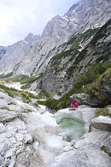 Mature female tourist sitting on rock by stream against mountains - ECPF00908