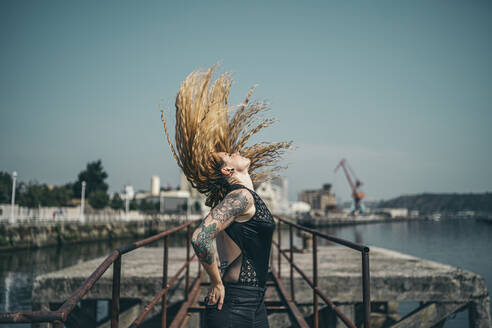 Side view of young tattooed woman tossing her long blond hair while standing hands in pockets on pier during sunny day - MTBF00390