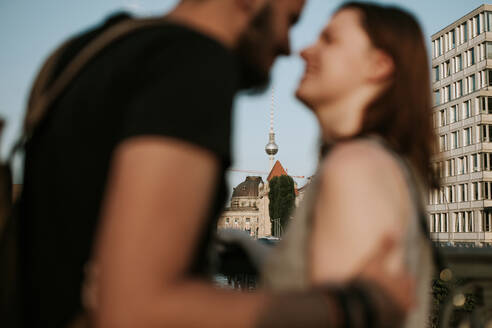 Affectionate young couple with Tv tower in background, Berlin, Germany - VBF00006