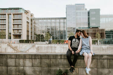 Young couple sitting on a wall at the riverbank, Berlin, Germany - VBF00021
