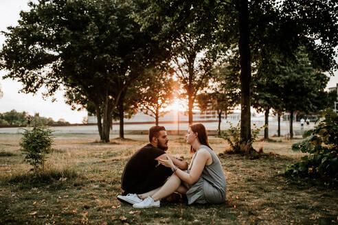 Young couple sitting in a park at sunset - VBF00027