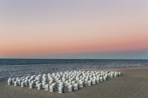 Hooded chairs at beach against sky during sunset, Ruegen, Germany - DIGF10485