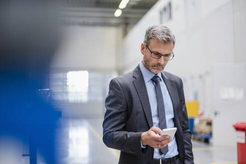 Mature businessman using cell phone in a factory - DIGF10555