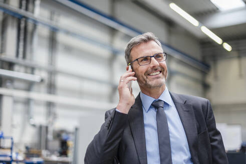 Smiling businessman on the phone in a factory - DIGF10558