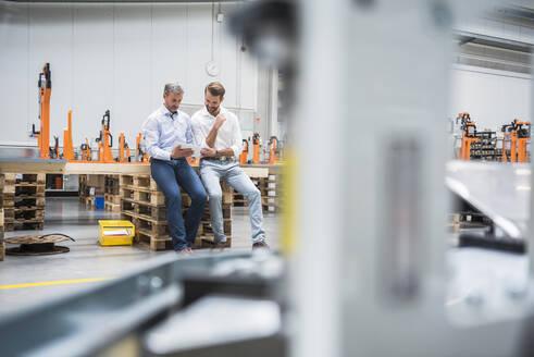 Two men sharing tablet on factory shop floor - DIGF10618