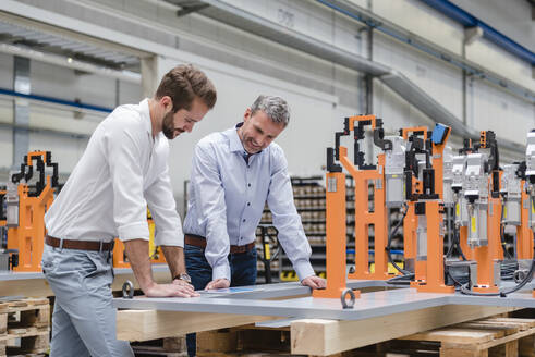 Two men looking at tablet on factory shop floor - DIGF10621
