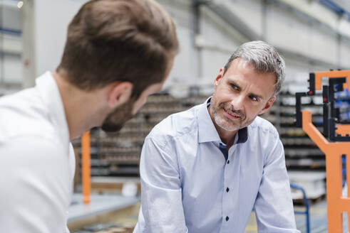 Portrait of mature man looking at colleague on factory shop floor - DIGF10624
