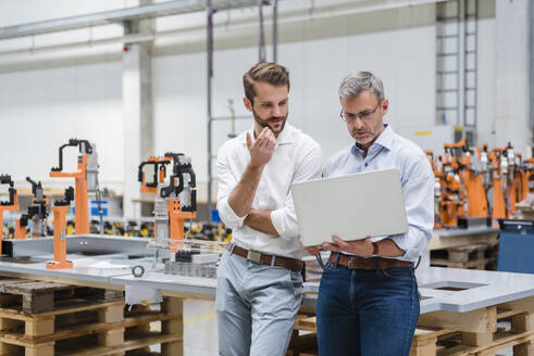 Two men using laptop on factory shop floor - DIGF10630