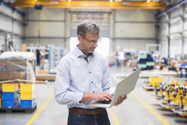 Mature man using laptop on factory shop floor - DIGF10633