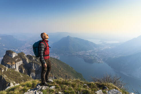 Rear view of hiker on mountaintop, Orobie Alps, Lecco, Italy - MCVF00305