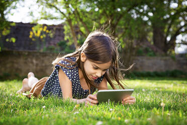 Smiling girl lying on meadow in the garden using digital tablet - LVF08871