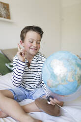 Portrait of smiling little boy sitting on bed with his globe - HMEF00924