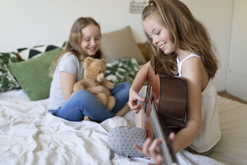 Smiling girl sitting on bed playing guitar while her sisters listening - HMEF00930