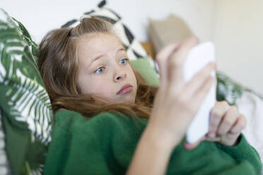 Portrait of girl wearing green pullover lying on bed starring at cell phone - HMEF00933