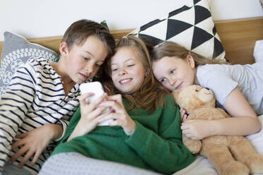 Group picture of three children lying together on bed looking at cell phone - HMEF00936